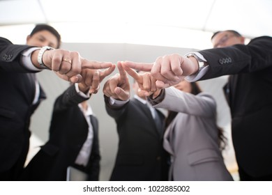 Business people pointing together at the center
