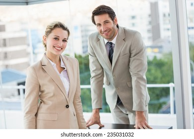 Business people posing and smiling at camera in office