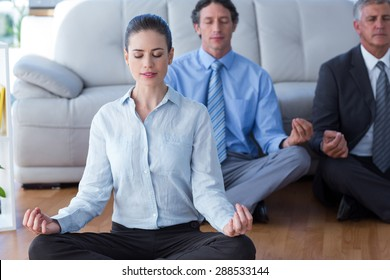 Business people practicing yoga in living room