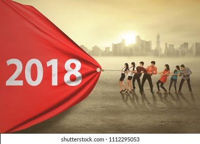Business people pulling numbers 2018 in the red banner while standing with a city background, symbolic of business effort for 2018