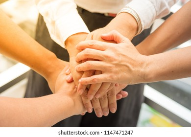 business people putting their hands together. Stack of hands. Close up top view, Unity and teamwork concept.