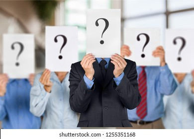 Business people with question marks on face on background