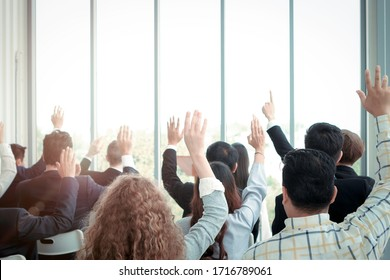 Business people raising hand up to ask question with speaker in seminar conference, raise hands up to agree or vote for comments in the meeting