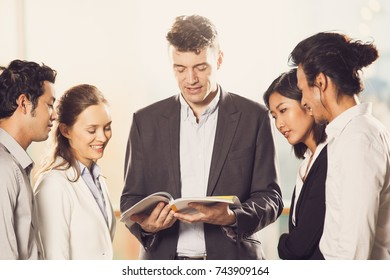 Business People Reading Book Together