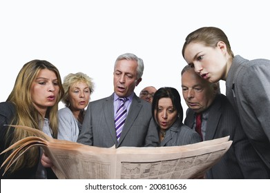 Business people reading newspaper against white background