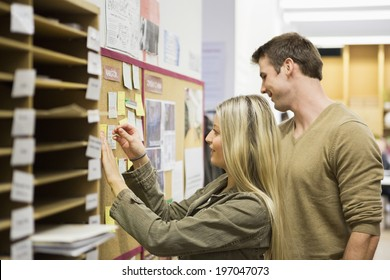 Business people reading reminders on bulletin board in office