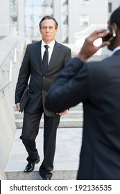 Business people. Rear view of African man in formal wear talking on the mobile phone while another businessman walking by stairs on background