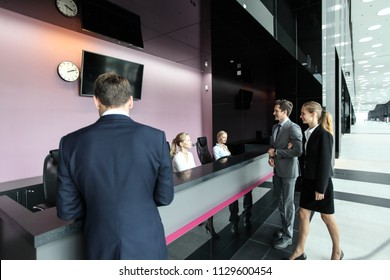 Business people at reception or front desk in office building, hotel or airport