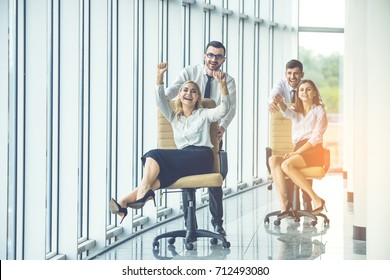 The business people ride on chairs in the office hall on the sunshine background