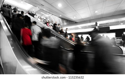 business people rushing on the escalator in motion blur on the subway station.