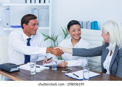 Business people shake hands during meeting in office