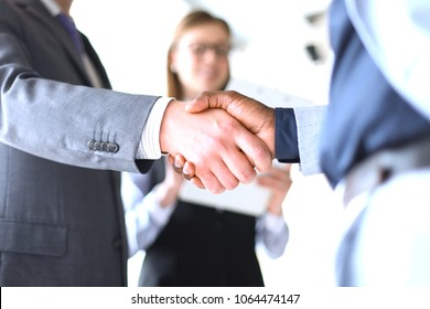 Business people shaking hands, finishing up a meeting. - Shutterstock ID 1064474147