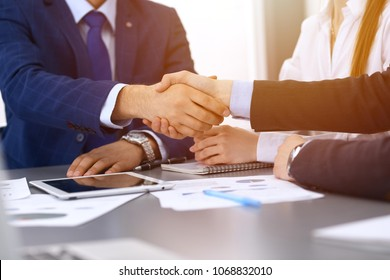Business people shaking hands, finishing up a papers signing. Meeting, contract and lawyer consulting concept