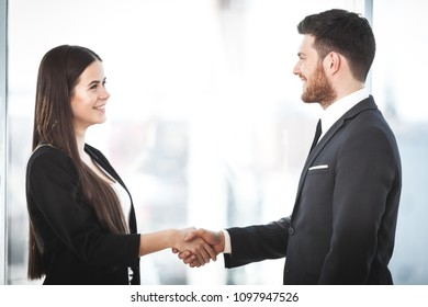 Business people shaking hands, finishing up a meeting in the office