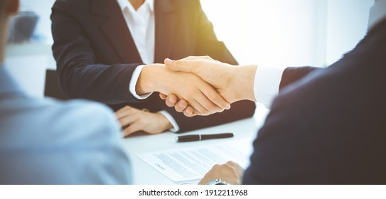 Business people shaking hands finishing up meeting or negotiation in sunny office. Business handshake and partnership concepts