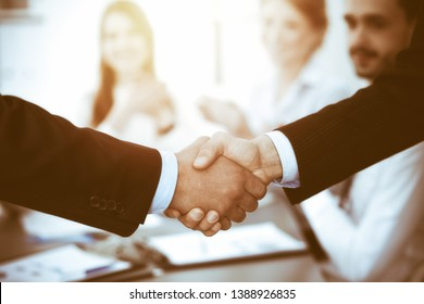 Business people shaking hands at meeting while theirs colleagues clapping and applauding. Group of unknown businessmen and women in modern white office. Success teamwork, partnership and handshake