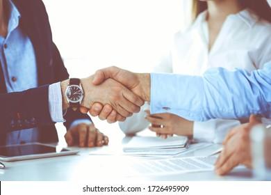 Geschäftsleute schütteln bei Treffen oder Verhandlungen die Hände, schließen sich. Gruppe unbekannter Geschäftsleute und Frauen im modernen Büro. Teamwork, Partnerschaft und Handshake-Konzept, tonisiertes Bild