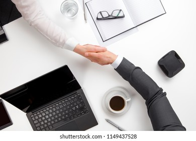 Business People Shaking Hands At Office Desk