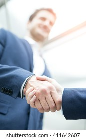 business people shaking hands with office window