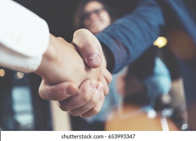 Business people shaking hands in the office after successful meeting. Three persons