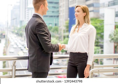 Business people shaking hands outdoor building view