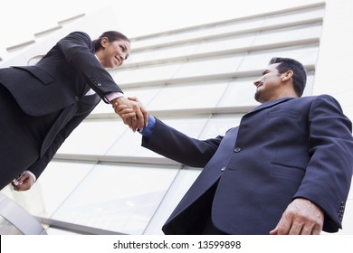 Business people shaking hands outside modern office