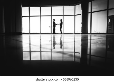 business people shaking hands over office background