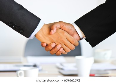 Business People Shaking Hands with Soft-Focus of Conference Table in the Background