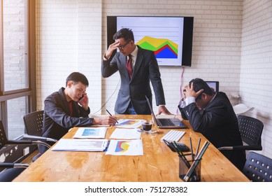 Business people show stressed of distress and anxiety about the company's performance as a downward curve in the meeting room.