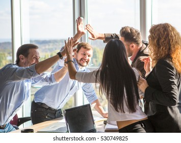 Business people showing team work and giving five after signing agreement or contract between companies, enterprises in office interior. Agreement or contract concept.