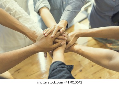 business people showing unity with their hands together, soft focus, vintage tone