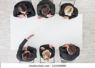 Business people sitting around empty table, business man pointing to blank copy space in the middle