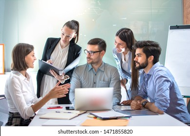 Business people sitting at meeting table in conference room discussing work and planning strategy.