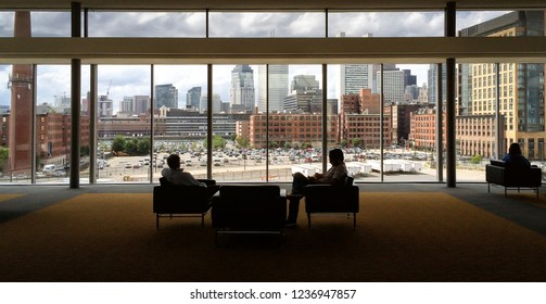 Business people sitting in a room in a convention center with big windows overlooking Boston, Massachusetts