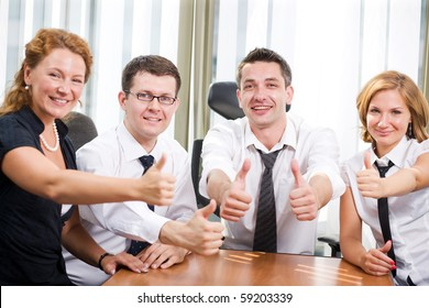 Business people sitting round table and expressing positivity and success with the help of thumb-ups. People smiling for the camera and sitting in board room in Hi Res.