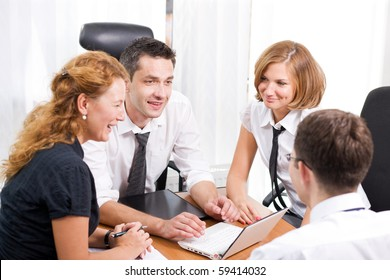Business people sitting round table in board room Hi Res. Two men and two women discussing business projects and business strategy all together.