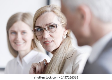 Business people sitting in a row and working, focus on mature woman in glasses
