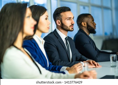 The business people sitting at the table in the meeting room