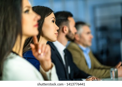 The business people sitting at the table in the office room