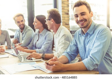 Business people in smart casual wear are participating in the conference, handsome man in the foreground is looking at camera and smiling