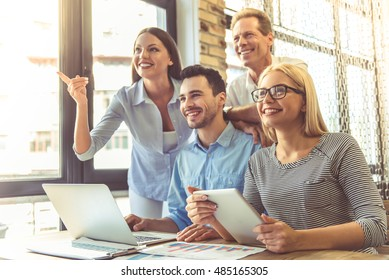 Business people in smart casual wear are using gadgets, looking away and smiling while working in the office. One lady is pointing