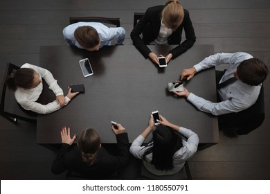 Business people with smartphones sitting around the table, top view