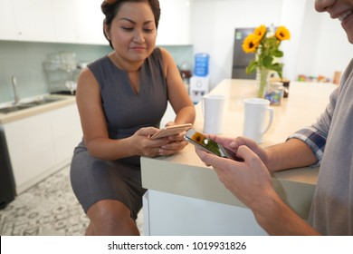 Business people with smartphones texting in office kitchen during break
