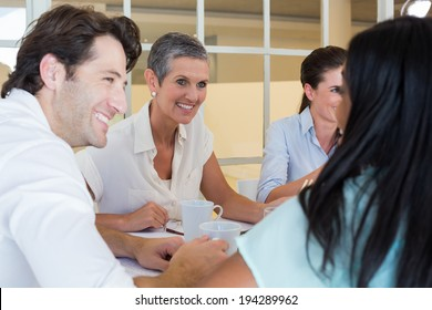 Business people smile and chat while enjoying hot drinks in the office