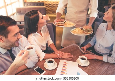 Business people are smiling and getting their order while having lunch in cafe