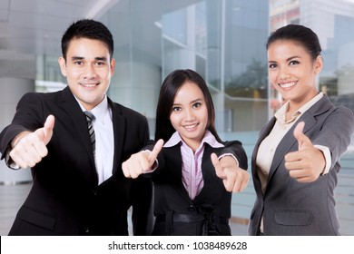 Business people smiling and showing thumbs up in a modern office