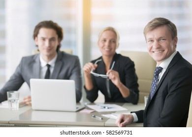 Business people, smiling, successful business partnership, discussing logo, website design, contract, negotiation room for rent. Portrait of mid aged businessman with subordinates at the background