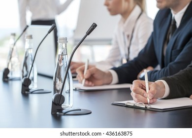 Business people speaking at presentation in microphones in office