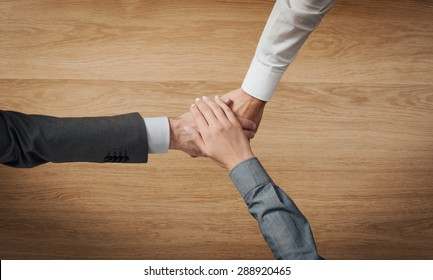 Business people stacking hands close up, wooden desktop on background, unrecognizable people