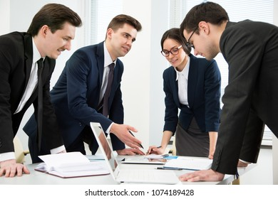 Business people are standing around a table in an office